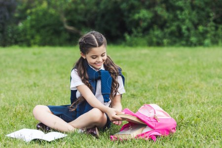 beautiful schoolgirl taking book out of backpack while sitting on grass in park