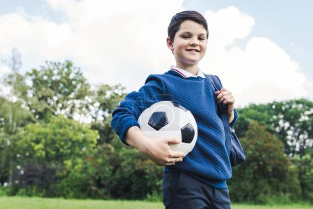 bottom view of kid holding soccer ball on grass field
