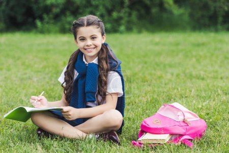 beautiful schoolgirl doing homework while sitting on grass in park