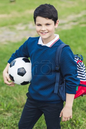 cute kid with soccer ball with soccer ball and backpack on grass field