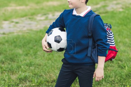cropped shot of kid with soccer ball with soccer ball and backpack on grass field