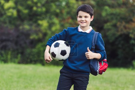 happy kid with soccer ball and backpack showing thumb up on grass field