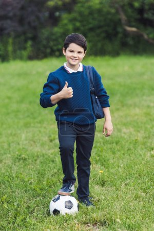 smiling kid with soccer ball and backpack showing thumb up on grass field