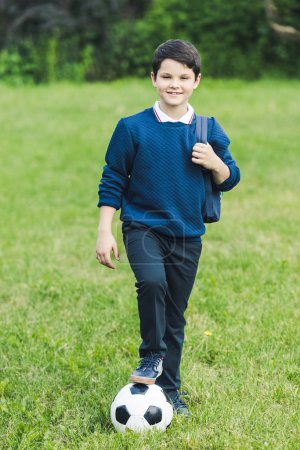 adorable kid with soccer ball and backpack on grass field