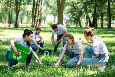 young volunteers cleaning green park together