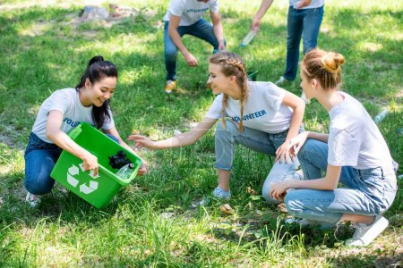 young volunteers cleaning green lawn in park together