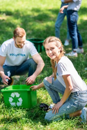 couple of smiling volunteers cleaning lawn with recycling box