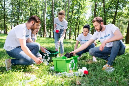young volunteers with green recycling box cleaning park together