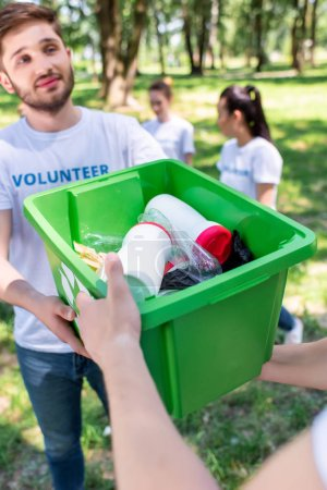 male volunteers with green recycling box in park