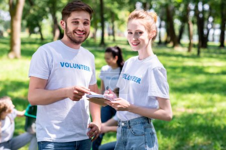 smiling couple holding textbook while volunteers cleaning park
