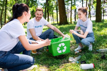 young smiling volunteers with green recycling box in park