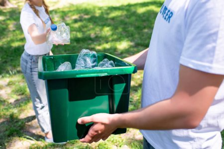 cropped view of couple of volunteers with recycling box cleaning park
