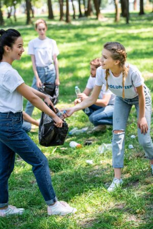 young volunteers cleaning lawn in park together