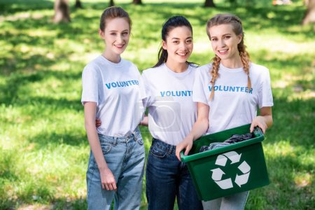 young volunteers with green recycling box for trash