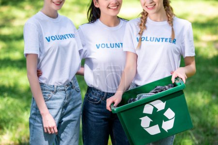 cropped view of young female volunteers with green recycling box