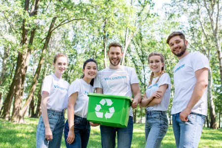 young happy volunteers with green recycling box in park