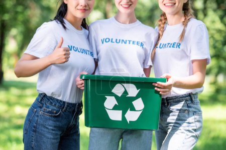 cropped view of young volunteers with green recycling box showing thumb up