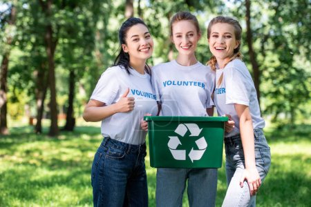 young female volunteers with recycling box showing thumb up