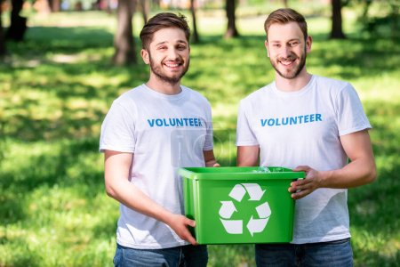 young male volunteers with green recycling box