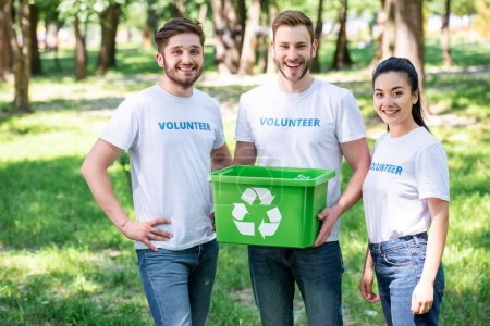 young volunteers with green recycling box standing in park