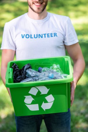 partial view of smiling volunteer holding recycling box with plastic waste