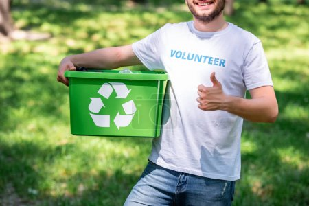 cropped view of man holding recycling box and showing thumb up