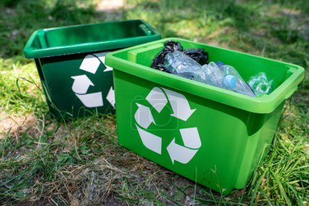 Photo for Green recycling boxes with plastic trash standing on lawn - Royalty Free Image