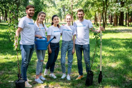 smiling volunteers with new trees, watering can and shovel standing in park