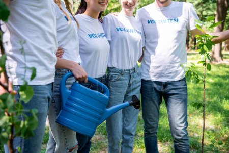 cropped view of volunteers with watering can and new trees in park