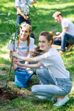 Photo pour Amis, le bénévolat et la plantation de nouveaux arbres dans le parc - image libre de droit