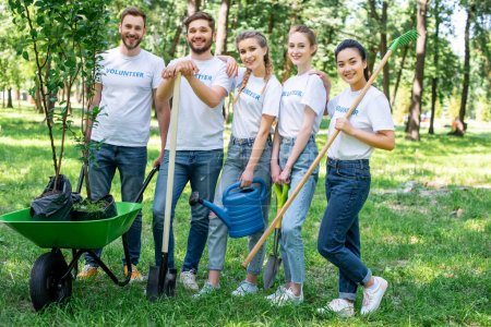 young volunteers posing in park with watering can, shovel, rake and wheelbarrow with new trees
