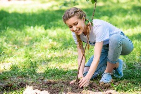 Photo pour Séduisante bénévole plantation nouvelle arborescence dans le parc - image libre de droit