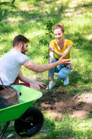 happy young couple planting new tree in park together