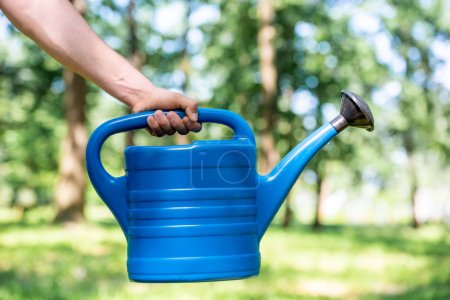partial view of man holding blue watering can