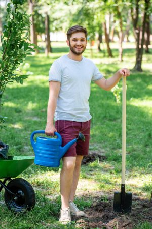 man with watering can and shovel standing in park with new trees in wheelbarrow