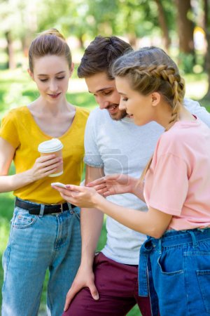 young friends with disposable cup of coffee using smartphone in park