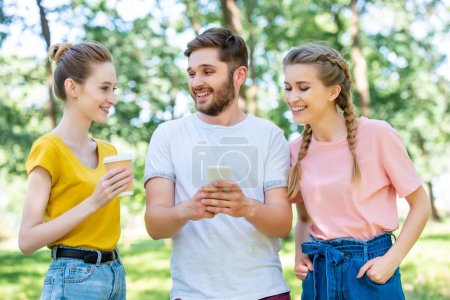 smiling friends with coffee to go using smartphone together in park