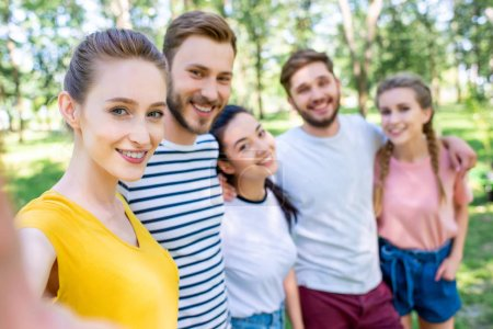 young happy friends taking selfie together in park