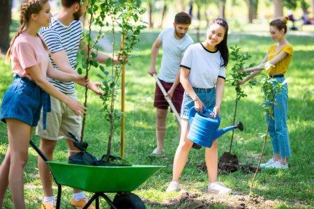 Photo pour Sourire des amis plantation de nouveaux arbres et de bénévolat dans le parc ensemble - image libre de droit