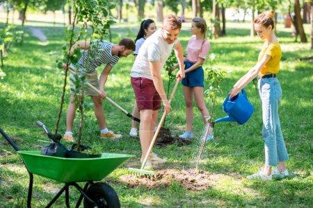 Photo pour Jeunes amis plantant de nouveaux arbres et faisant du bénévolat dans le parc - image libre de droit