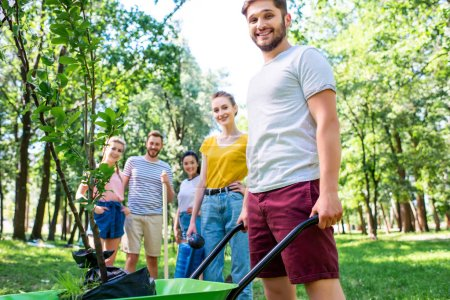 young friends with wheelbarrow and new trees volunteering in park