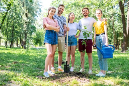 friends with watering can and shovel planting new tree and volunteering in park