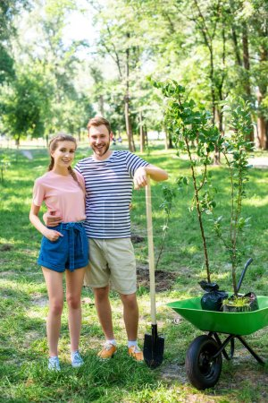 couple hugging while planting trees in park