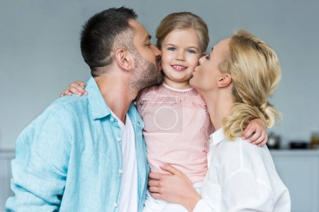 happy parents kissing adorable little daughter at home