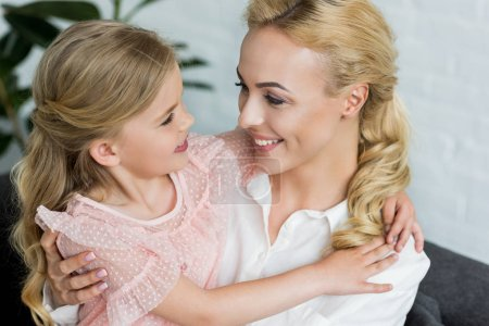 Photo for Beautiful happy mother and daughter hugging and smiling each other at home - Royalty Free Image