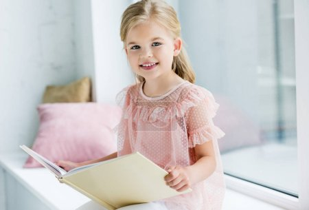 adorable child holding book and smiling at camera while sitting on windowsill