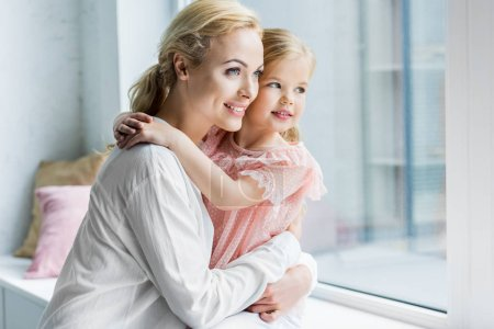 Photo for Beautiful happy mother and daughter hugging and looking at window - Royalty Free Image