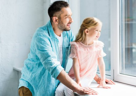 happy father and cute little daughter looking at window together at home