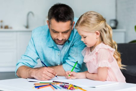 father and adorable little daughter drawing with colored pencils together at home