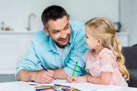 happy father and daughter smiling each other while drawing together at home
